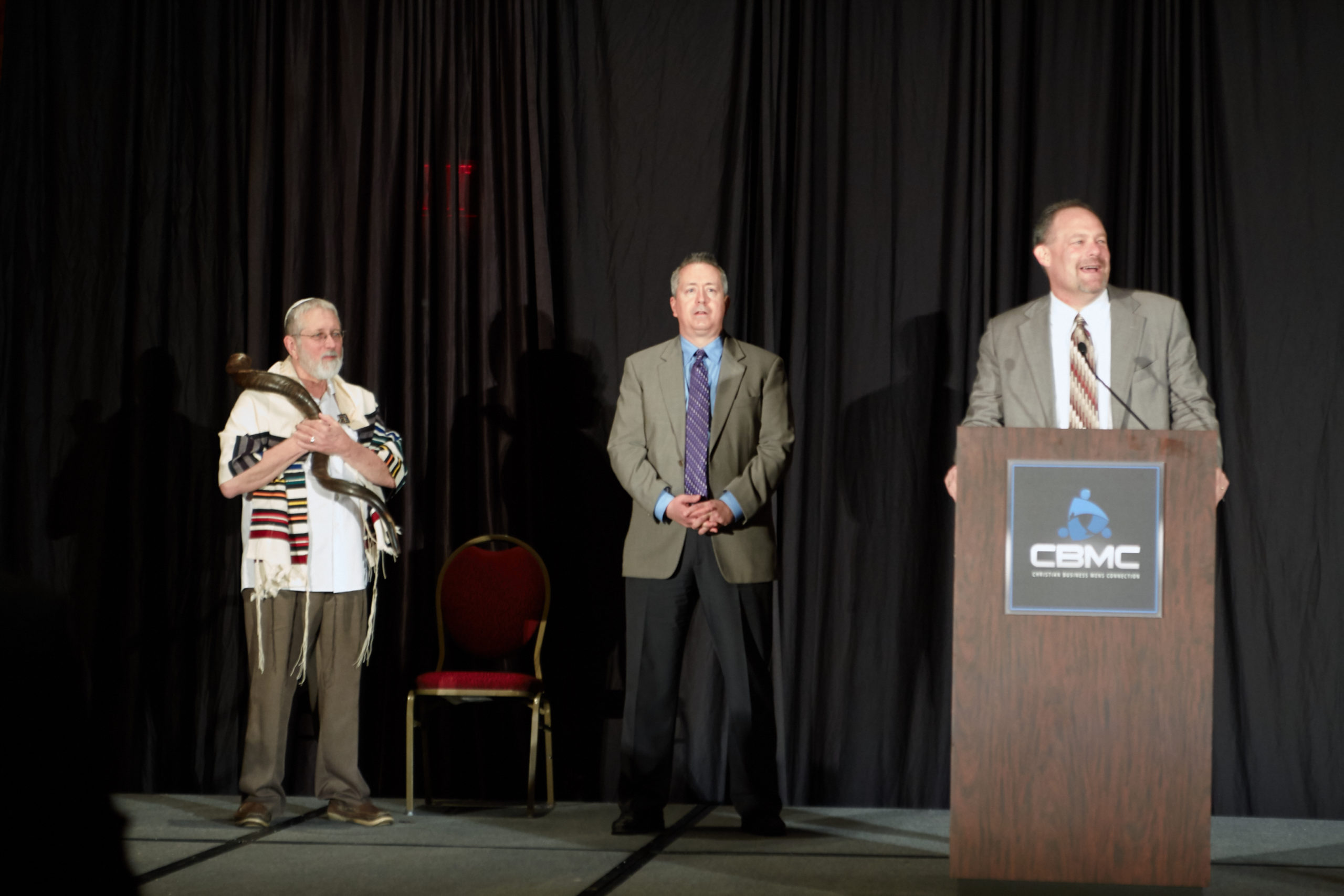 Rabbi with shofar, two other men, one behind a podium  Omaha Leadership Prayer Breakfast